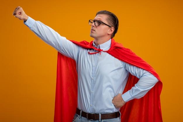 Homme d'affaires de super héros en cape rouge et lunettes à la recherche de côté en gardant le bras en geste de vol prêt à aider debout sur un mur orange