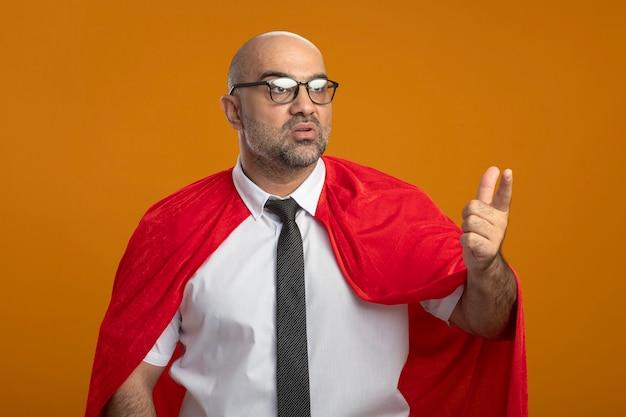 Homme d'affaires de super héros en cape rouge et lunettes regardant de côté confus en montrant quelque chose avec index figner