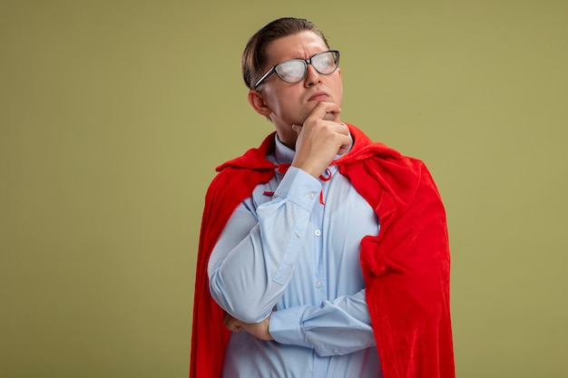 Homme d'affaires de super héros en cape rouge et lunettes regardant de côté avec la main sur le menton pensant debout sur un mur léger