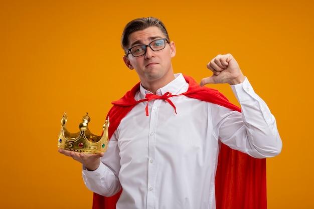 Homme d'affaires de super héros en cape rouge et lunettes tenant la couronne pointant sur lui-même souriant confiant debout sur le mur orange