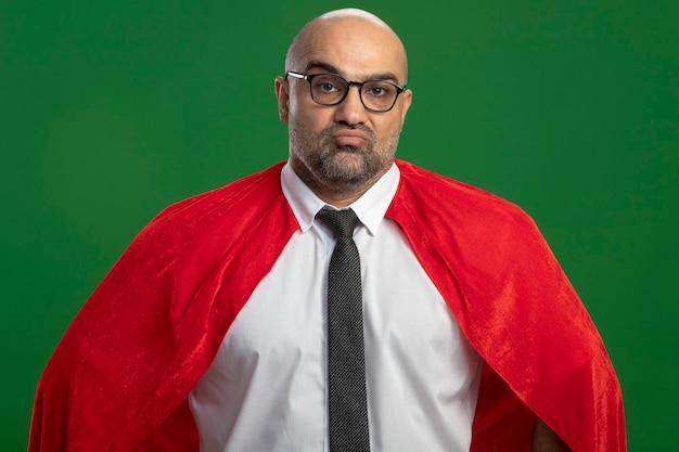 Homme d'affaires de super héros en cape rouge et lunettes avec visage sérieux