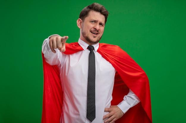 Homme d'affaires de super héros en cape rouge pointant avec index souriant confiant debout sur mur vert