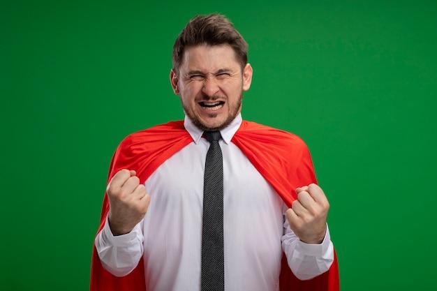 Homme d'affaires de super héros en cape rouge serrant les poings émotionnels et excités debout sur fond vert