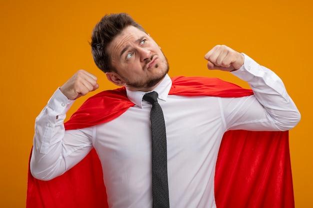 Homme d'affaires de super héros en cape rouge, serrant les poings montrant la force et le courage à la confiance debout sur le mur orange