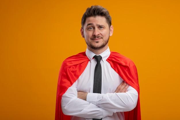 Homme d'affaires de super héros en cape rouge souriant confiant avec les bras croisés sur la poitrine debout sur le mur orange