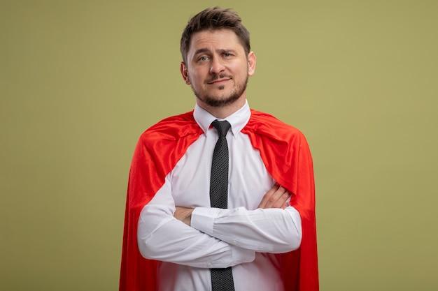 Homme d'affaires de super héros en cape rouge souriant confiant avec les bras croisés sur la poitrine debout sur le mur vert