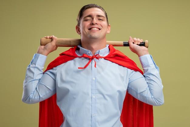 Homme d'affaires de super héros en cape rouge tenant derrière son cou souriant confiant debout sur mur léger