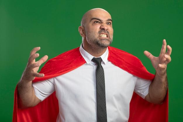 Homme d'affaires de super héros en cape rouge va sauvage en levant les mains avec une expression agressive debout sur un mur vert