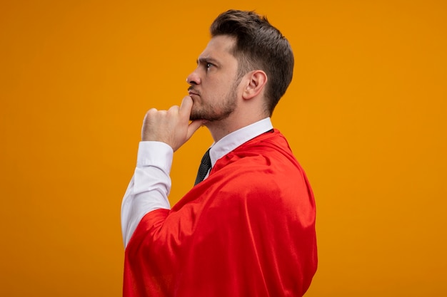Homme d'affaires de super héros en capestanding rouge sur le côté avec une expression pensive sur le visage avec la main sur le menton thinkover mur orange