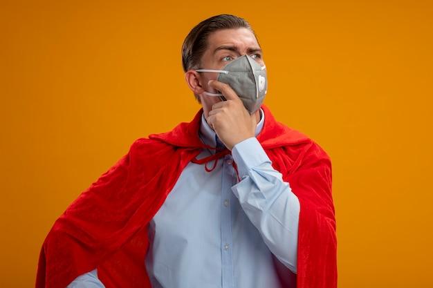 Homme d'affaires de super héros en masque facial protecteur et cape rouge à côté avec une expression pensive sur le visage avec la main sur le menton pensant debout sur fond orange