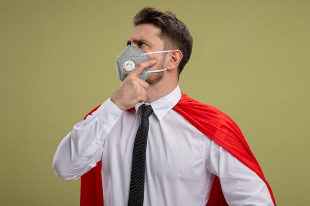 Homme d'affaires de super héros en masque facial protecteur et cape rouge à côté avec une expression pensive sur le visage avec la main sur le menton pensant debout sur le mur vert