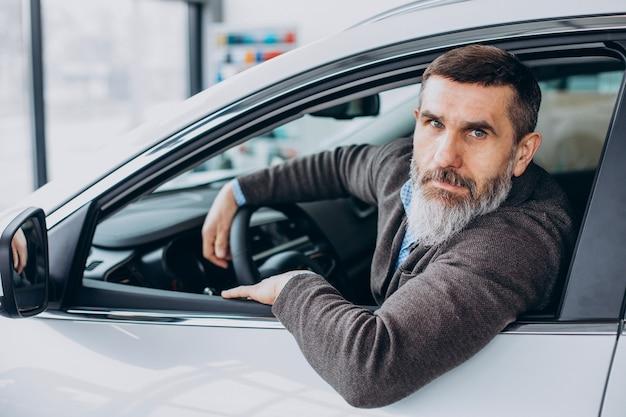 Homme d'affaires supérieur choisissant une voiture dans la salle d'exposition de voiture