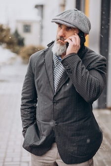 Homme d'affaires supérieur utilisant le téléphone dans la rue