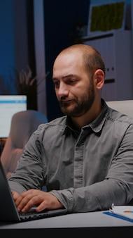 Homme d'affaires surmené tapant des statistiques financières sur un ordinateur portable assis à une table de bureau