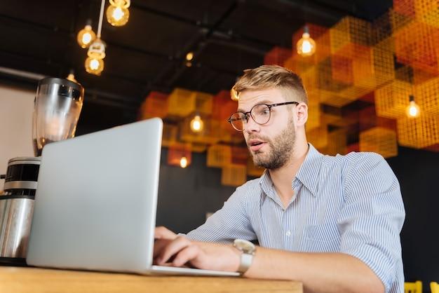 Homme d'affaires surpris. homme aux yeux bleus portant des lunettes se sentant surpris après avoir lu des informations