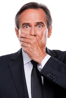 Homme d'affaires surpris. homme mûr surpris en tenue de soirée couvrant la bouche avec la main et regardant la caméra en se tenant debout isolé sur fond blanc