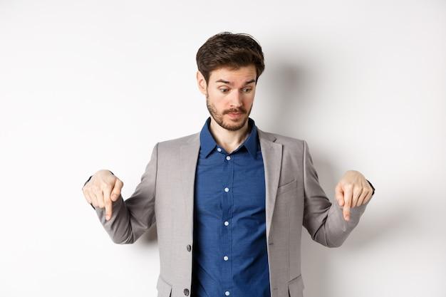 Homme d'affaires surpris à la recherche et pointant vers le bas avec des sourcils levés