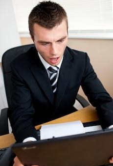Homme d'affaires surpris en regardant son ordinateur portable