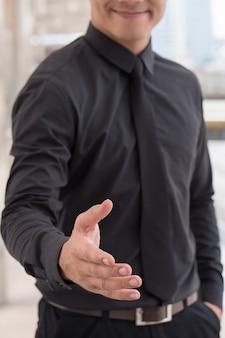 Homme d'affaires sympathique offrant un concept de coopération de poignée de main