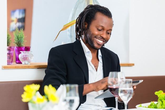 Homme d'affaires avec tablette au restaurant