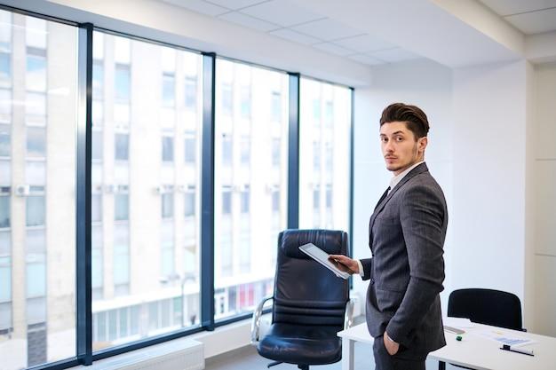 Homme d'affaires avec une tablette dans les mains du bureau sur le backgrou