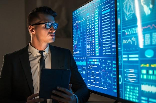 L'homme d'affaires avec une tablette dans ses mains debout près d'écrans bleus