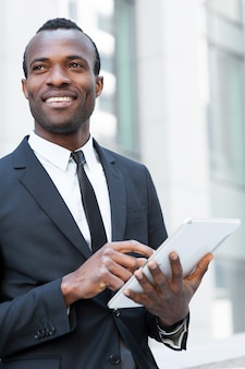 Homme d'affaires avec tablette numérique. jeune homme africain confiant en tenue de soirée travaillant sur une tablette numérique et regardant ailleurs avec le sourire tout en se tenant à l'extérieur