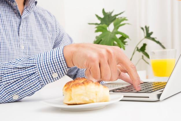 Homme d'affaires en tapant sur un ordinateur portable avec du pain et un verre de jus sur la table