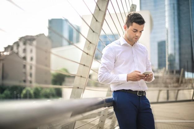 Homme d'affaires tapant sur son téléphone, debout dans la rue