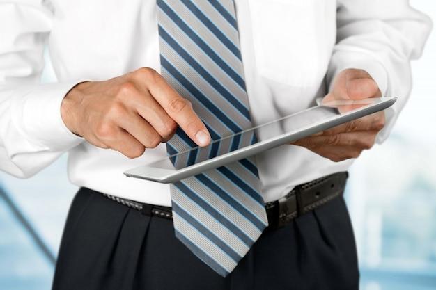 L'homme d'affaires a tapé sur la table numérique sur l'arrière-plan flou