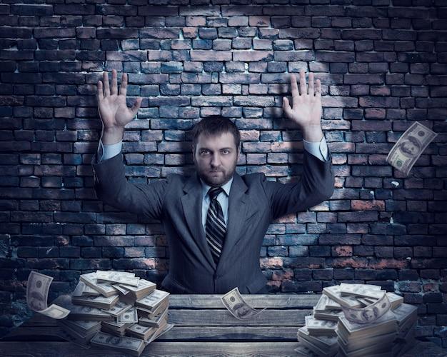 Homme d'affaires avec des tas d'argent sur le mur de briques