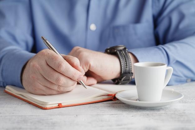 Homme d'affaires avec une tasse de café écrit quelque chose sur le papier