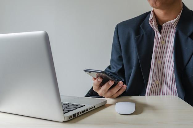 Homme d'affaires avec un téléphone intelligent à la recherche d'informations sur le travail et de la recherche sur internet sur un ordinateur portable sur le bureau