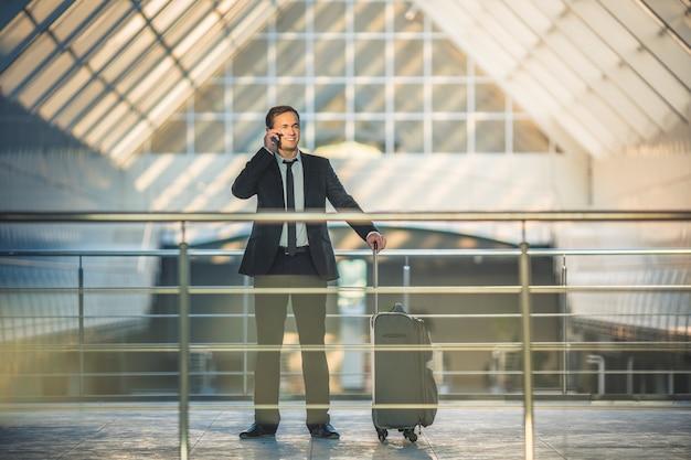 L'homme d'affaires avec un téléphone de valise dans le centre d'affaires