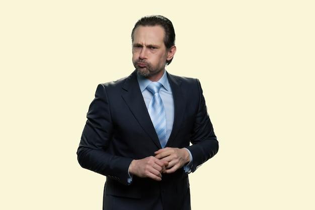 Homme d'affaires tenant de l'air dans la bouche. un homme mûr sérieux en costume endure une douleur isolée sur fond jaune.