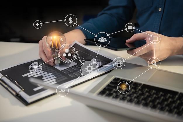 Homme d'affaires tenant des ampoules, des idées de nouvelles idées avec une technologie innovante et de la créativité au bureau à domicile.