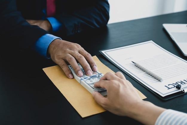 Homme d'affaires tenant un billet de banque en dollars pour soudoyer les responsables financiers concept anti-corruption
