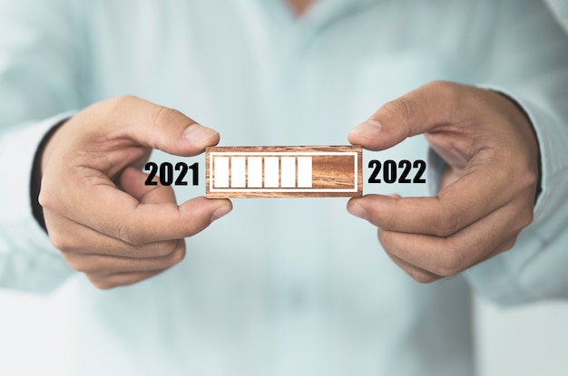 Homme d'affaires tenant un bloc de cube en bois avec barre de progression de chargement pour le réveillon du nouvel an et changeant l'année 2021 à 2022.