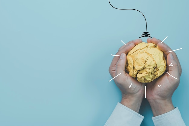Homme d'affaires tenant une boule de papier brouillon jaune avec peinture d'illustration pour ampoule virtuelle. c'est une idée de pensée créative et un concept d'innovation.