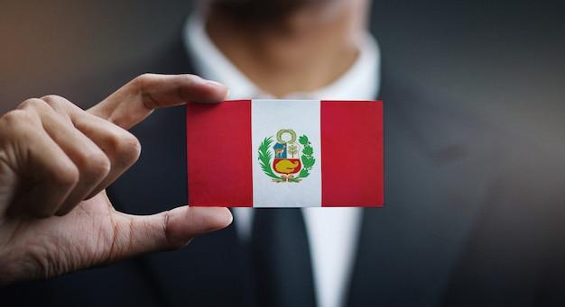 Homme d'affaires tenant une carte drapeau du pérou