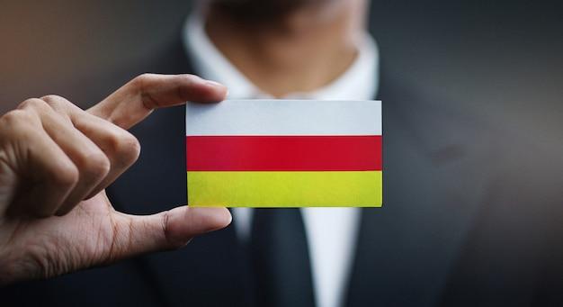 Homme d'affaires tenant une carte drapeau ossétie du nord-alanie