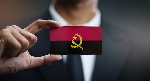 Homme d'affaires tenant une carte du drapeau angolais