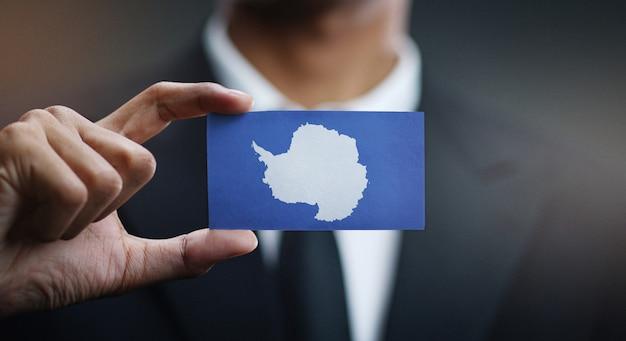 Homme d'affaires tenant une carte du drapeau de l'antarctique