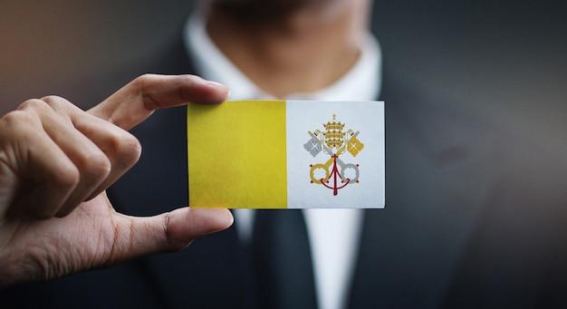 Homme d'affaires tenant une carte du drapeau de la cité du vatican