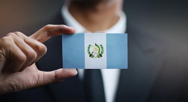 Homme d'affaires tenant une carte du drapeau du guatemala