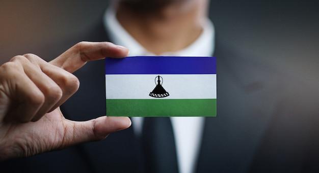 Homme d'affaires tenant une carte du drapeau du lesotho