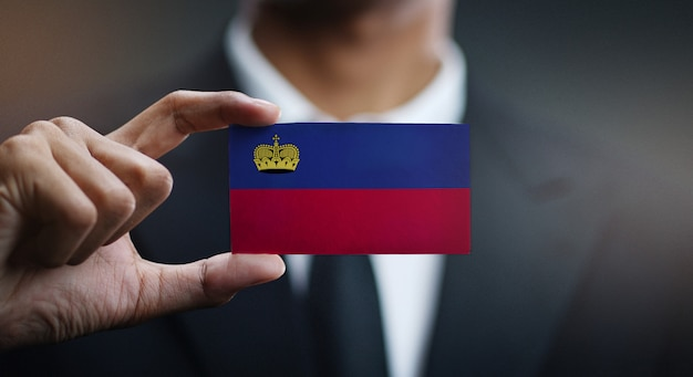Homme d'affaires tenant une carte du drapeau du liechtenstein