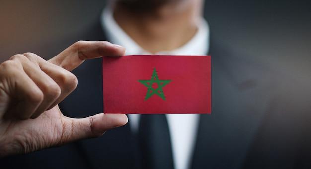 Homme d'affaires tenant une carte du drapeau du maroc