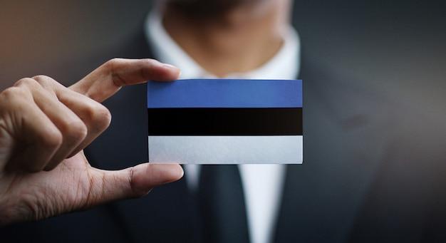 Homme d'affaires tenant une carte du drapeau de l'estonie