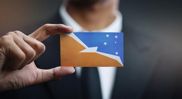 Homme d'affaires tenant la carte du drapeau de la terre de feu